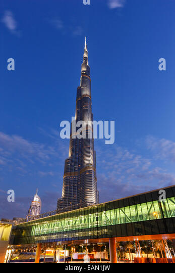 Modern architecture. Gangway to Dubai Mall and the tallest building  Burj Khalifa on the background in Dubai. - Stock Image
