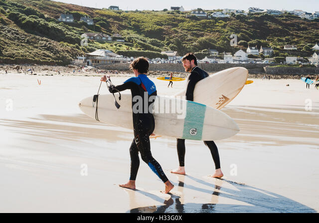 Two young men carrying the boards up the beach after surfing at Sennen Cove, Cornwall - Stock Image