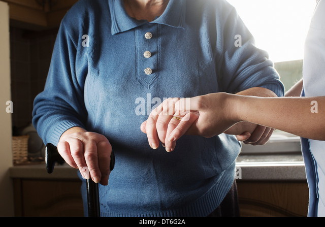 Personal care assistant supporting senior woman to walk - Stock Image