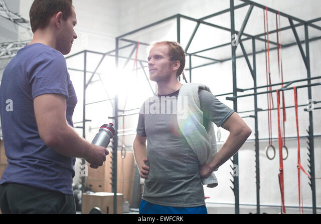 Male friends talking in crossfit gym - Stock-Bilder