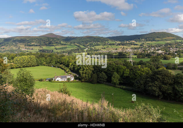 House with solar panels in rural setting with Sugar Loaf mountain in distance near Abergavenny, Wales, UK - Stock Image