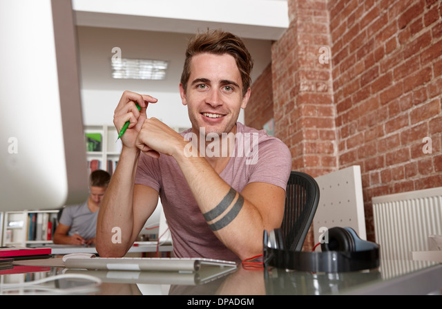 Portrait of young man at desk - Stock Image