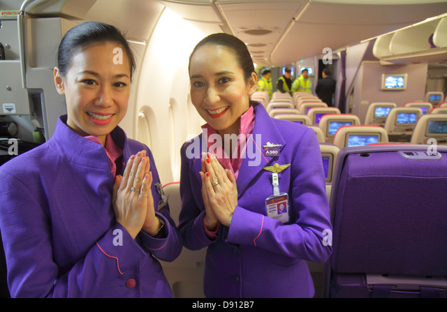 Germany Frankfurt am Main Airport FRA arriving Thai Airways cabin Asian woman attendants uniform wai greeting respect - Stock Image
