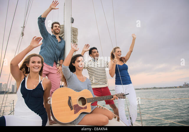 Friends on sailing boat waving, woman with guitar - Stock Image