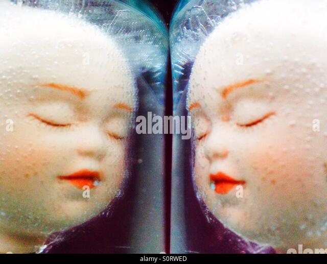 A mirror image of doll faces. - Stock Image