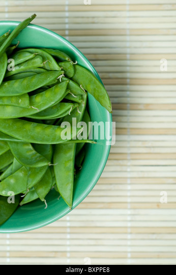 Bowl of snow peas in pod - Stock Image