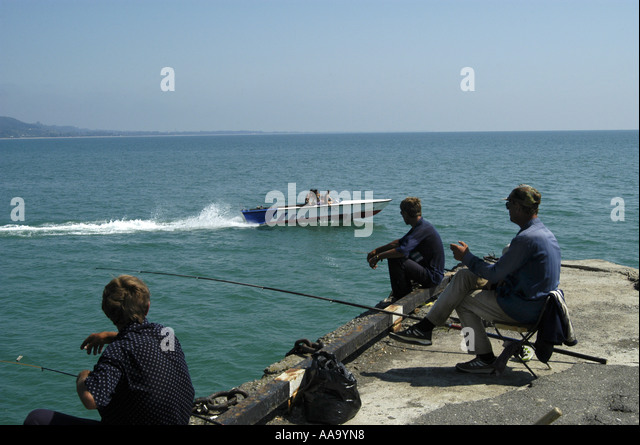 Fishermen watching a speed boat in the harbour of Sukhumi, capital of Abkhazia. - Stock Image