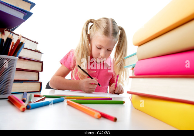 Portrait of cute girl sitting among stacks of literature and drawing - Stock Image