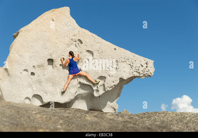 France, Corsica, Young woman climbing big rock - Stock Image