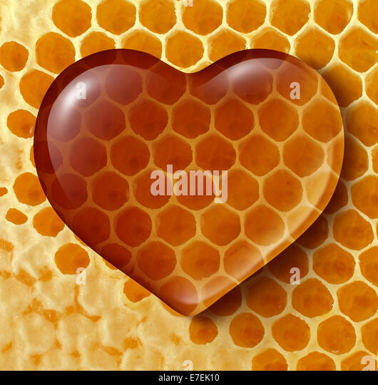 Healthy food love concept as liquid honey shaped as a heart on a honeycomb or honey comb background created by bees - Stock-Bilder