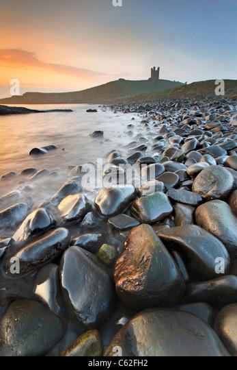 Dunstanburgh Castle captured at dawn. - Stock Image