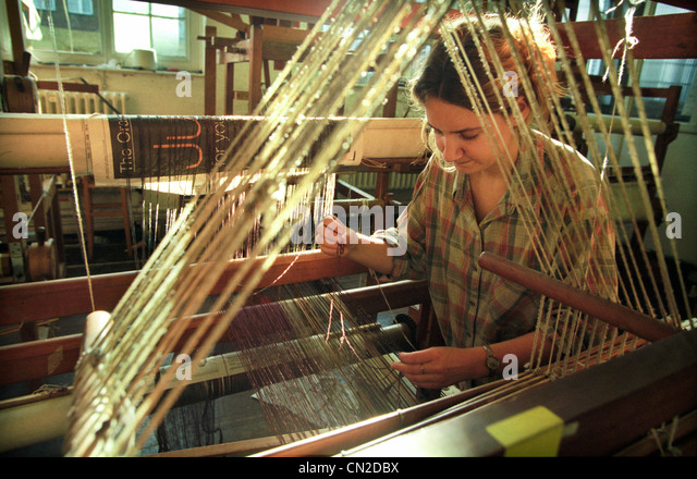 A University of Brighton textile student inspects the wool threads on a loom as part of her degree course. - Stock Image
