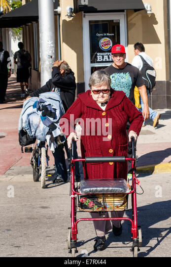 Miami Beach Florida senior woman walker disabled crossing street health aging elderly - Stock Image