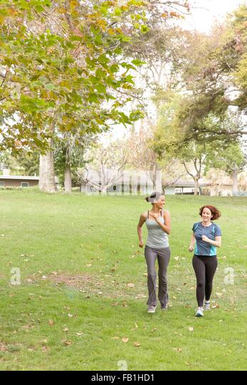 Full length front view of women wearing sport clothing running on grass - Stock Image
