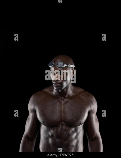 Studio shot of a fit young swimmer against black background. Muscular African athlete looking away at copy space. - Stock Image