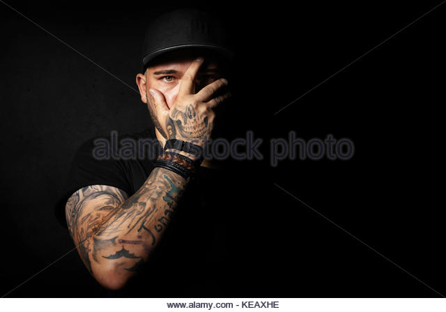 Skull tattoo on  hand covering and forming part of a young man's face - Stock Image
