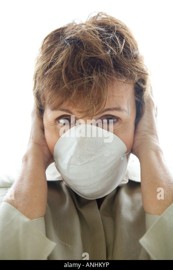 Woman with hands over ears wearing pollution mask, looking at camera - Stock Image