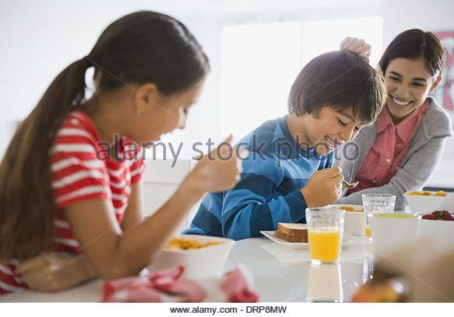 Siblings eating breakfast together - Stock Image