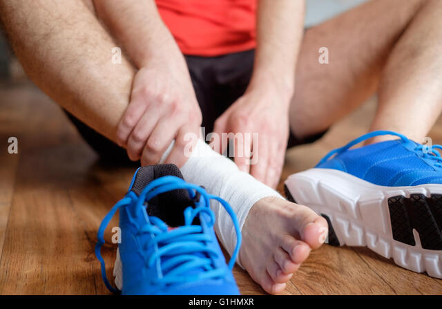 sportsman massaging his injured ankle after a sport accident - Stock-Bilder