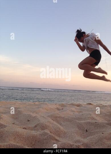 Woman Jumping On The Beach - Stock Image