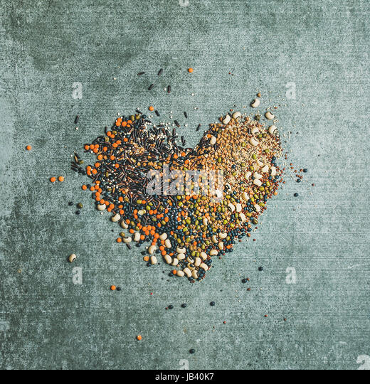 Various raw grains, beans, cereals in shape of heart - Stock Image