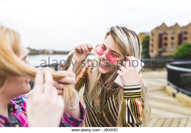 Two female friends, outdoors, pulling hair across lip to make moustache - Stock-Bilder