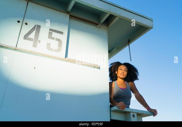 Mid adult woman standing on look out tower at beach, looking at view - Stock Image