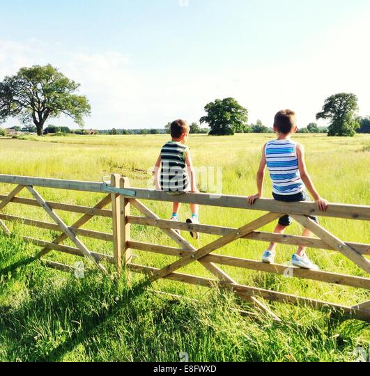 Two boys (6-7) sitting on gate - Stock Image