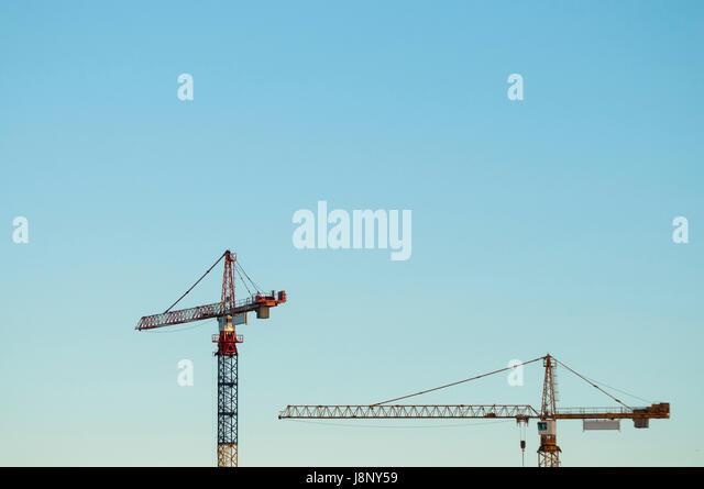 Construction cranes against clear sky - Stock-Bilder