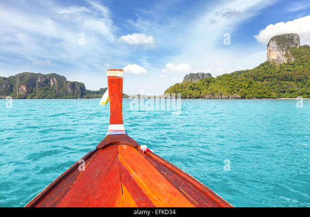 Wooden boat and a tropical island in distance. - Stock Image