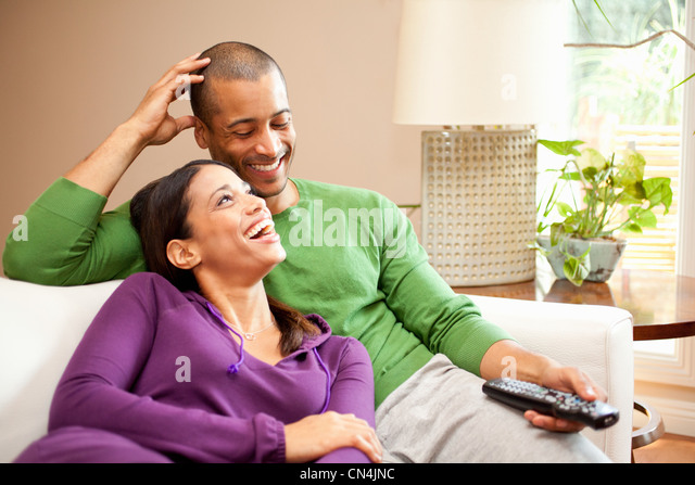 Happy couple relaxing and watching television - Stock Image