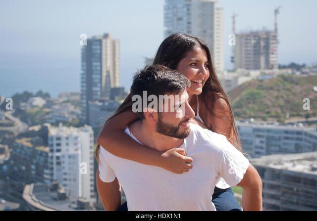 Hispanic man carrying woman piggyback in city - Stock Image