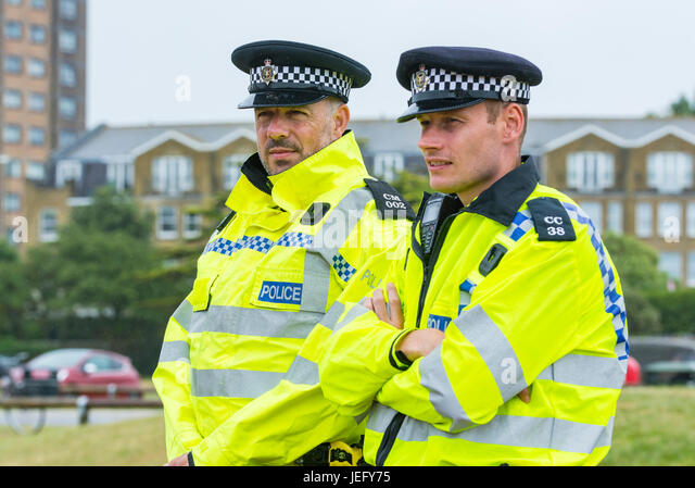 Pair of male police officers keeping watch at an outdoor event in the rain. UK Sussex Police officers. - Stock Image