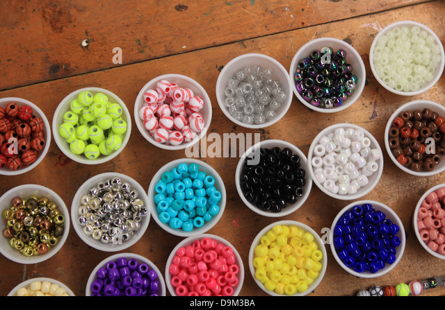Beads sorted into cups on a craft table - Stock Image