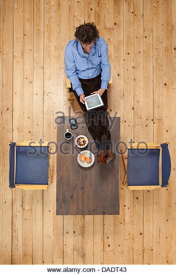 Overhead view of male in studio space using digital tablet - Stock Image