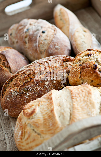 Various kinds of fresh baked bread loaves in wooden tray - Stock Image