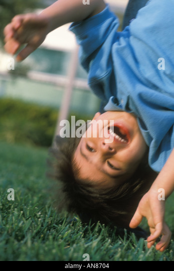 Upside down 3 year old mixed Caucasian Hispanic Asian boy - Stock Image