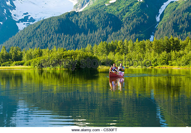 Two people canoeing in a tandem canoe, Chugach Mountains in the background, Portage Valley, Chugach national Forest, - Stock Image