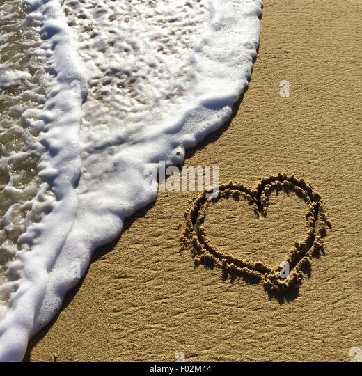 Heart shape drawn in the sand on a beach - Stock-Bilder