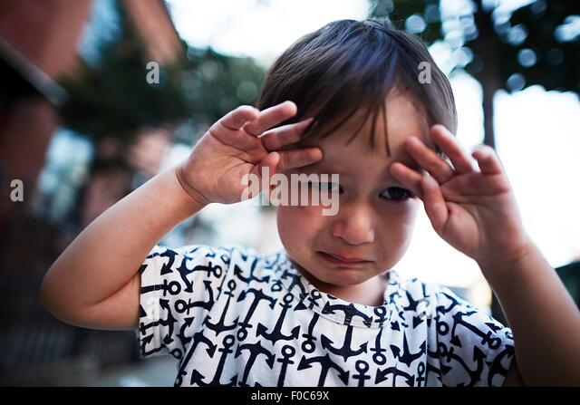 Portrait of boy crying on street - Stock Image