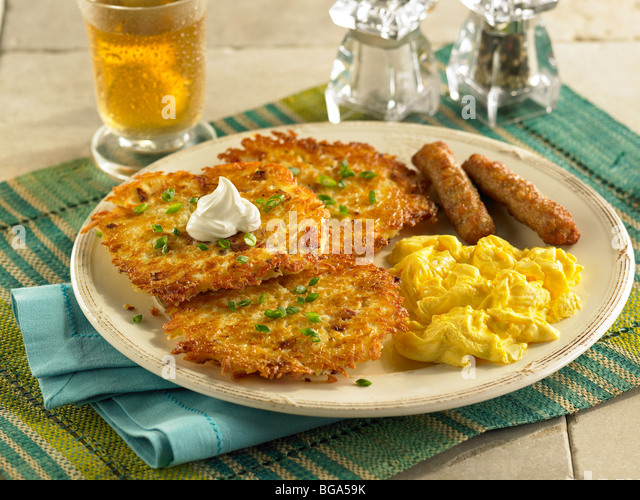 Potato pancakes with scrambled eggs and sausage - Stock Image