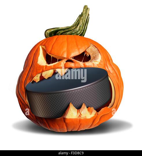Hockey in autumn concept as a pumpkin jack o lantern biting into a hard black ice puck as a symbol for halloween - Stock-Bilder