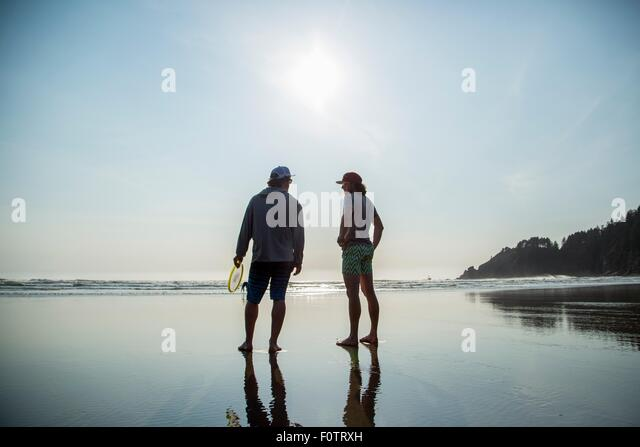 Rear silhouetted view of two young men chatting on Short Sands Beach, Oregon, USA - Stock Image