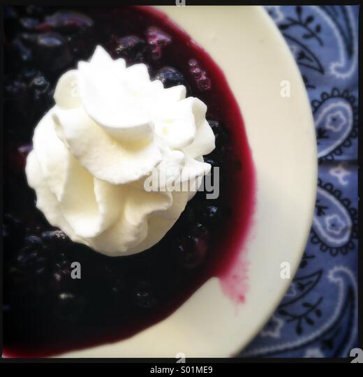 Warm Blueberries and Whipped Cream - Stock Image