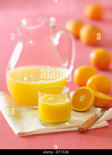 A glass pitcher of orange juice with a glass filled with fresh squeezed orange juice with several oranges in the - Stock Image