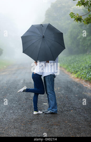romantic young couple hiding behind the umbrella in the rain - Stock Image
