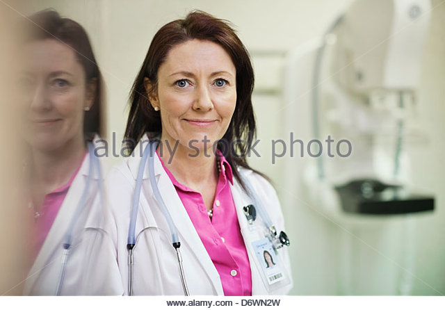 Portrait of beautiful doctor in lab coat with stethoscope around neck - Stock Image