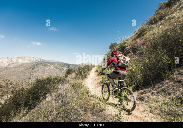 Downhill mountain biker climbing hill - Stock Image