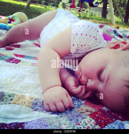 Sleeping baby napping outside on a quilt - Stock Image