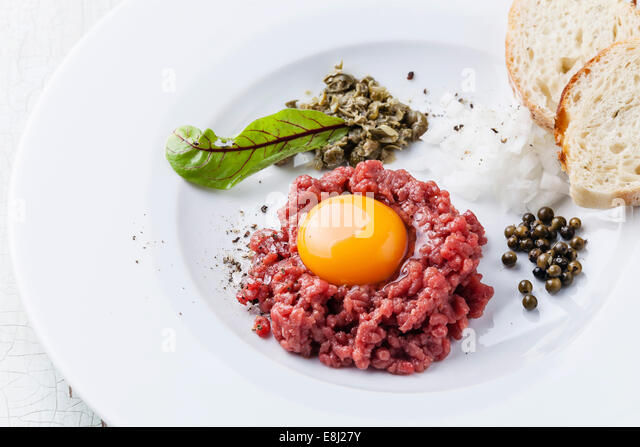 Beef tartare with capers and bread on white plate - Stock Image